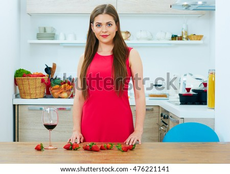 Smiling woman in red dress standing in kitchen.
