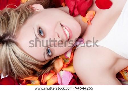 Smiling woman in rose petals - stock photo