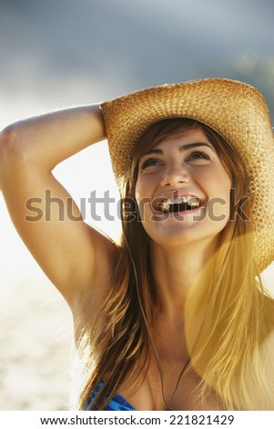 Smiling woman in straw cowboy hat - stock photo