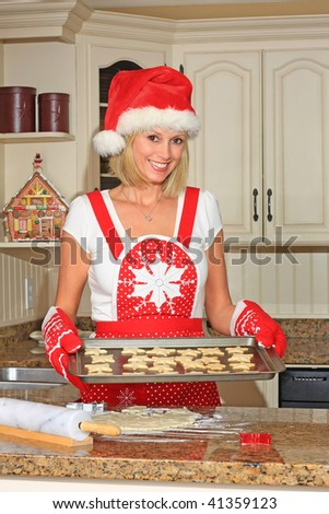 Smiling woman in the kitchen baking shortbread cookies. - stock photo