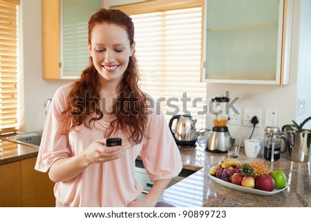 Smiling woman in the kitchen writing text message - stock photo