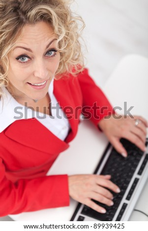 Smiling woman in the office looking up cheerfully - stock photo