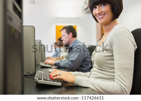 Smiling woman in the row of the computer class working - stock photo