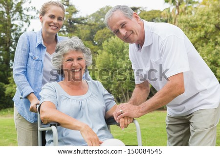 Smiling woman in wheelchair with daughter and husband looking at camera in the park - stock photo