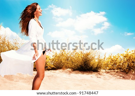 smiling woman in white dress and bikini standing on beach, sunny summer day - stock photo