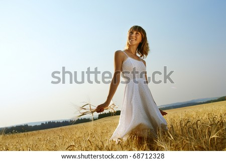 Smiling woman in white dress walking on field with ripe yellow wheat - stock photo