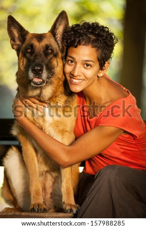 Smiling woman is hugging her german shepherd while seated on a bench - stock photo