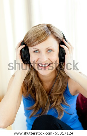 Smiling woman is listening the music in the living-room at home