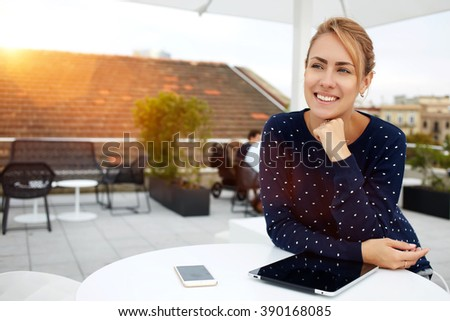 Smiling woman is sitting in comfortable cafe-bar with portable touch pad during her recreation time, cheerful happy female rests after work on digital tablet and waits her friends in cozy coffee shop - stock photo