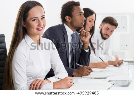 Smiling woman is sitting next to serious African American man and his colleagues. Concept of being possitive