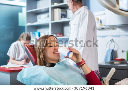 Smiling woman is taking a glass of water in dental office. Dentists in the background. - stock photo