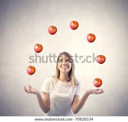 Smiling woman juggling with apples - stock photo