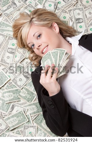 Smiling woman laying in money - stock photo