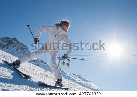 smiling woman learning skis in slopes