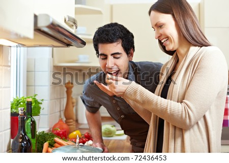 Smiling woman letting man taste a soup with a wooden spoon in the kitchen