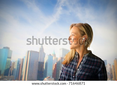Smiling woman listening to music with cityscape on the background - stock photo