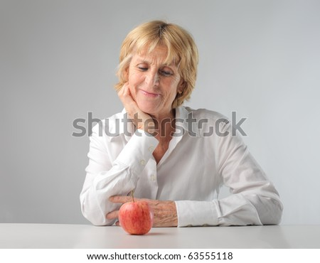 Smiling woman looking at an apple - stock photo