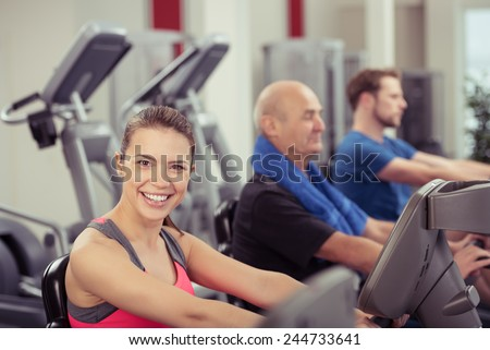 Smiling Woman Looking at Camera Using Recumbent Exercise Bike in Busy Gym - stock photo