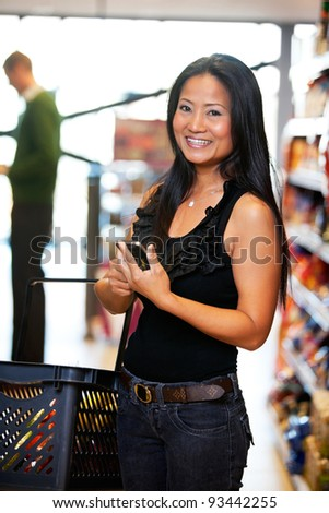 Smiling woman looking at camera while holding mobile phone in hand with man in the background - stock photo