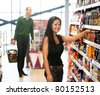 Smiling woman looking at camera with man in the background in shopping store - stock photo