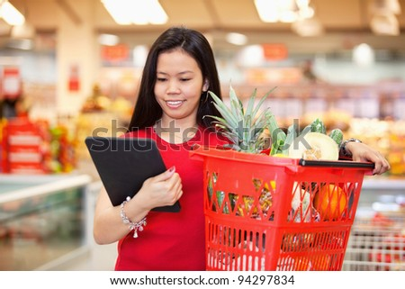 Smiling woman looking at digital tablet and holding fruit basket in shopping centre - stock photo