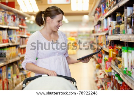 Smiling woman looking at digital tablet in shopping centre while holding baby stroller - stock photo
