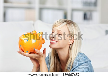 Smiling woman looking at her colourful yellow piggy bank dreaming of what she will do with her savings