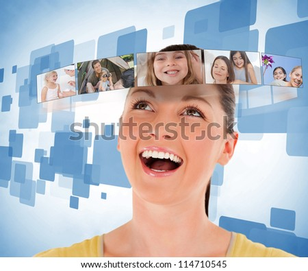 Smiling woman looking at picture bar on blue background - stock photo