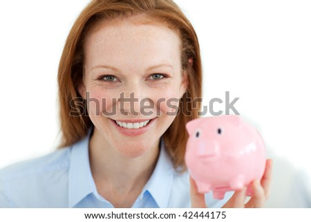 Smiling woman looking at the camera holding a piggy bank