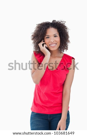 Smiling woman looking at the camera while calling against a white background