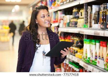 Smiling woman looking at the products while holding digital tablet with people in the background - stock photo