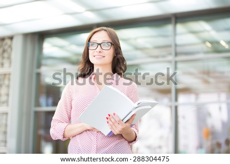 Smiling woman looking away while holding outside building - stock photo
