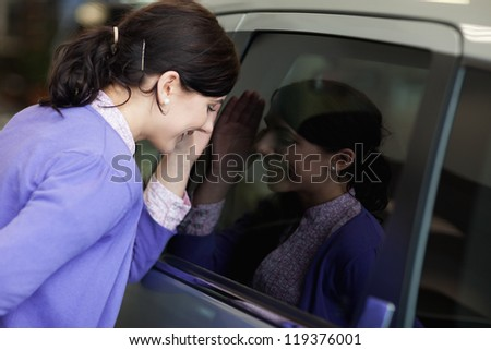 Smiling woman looking inside a car
