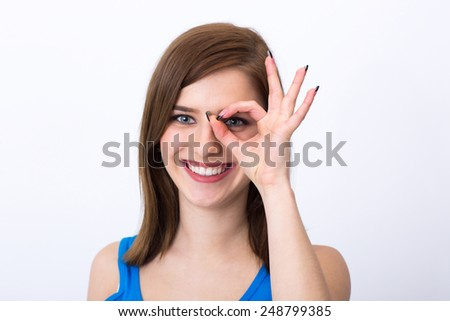 Smiling woman looking through a hole in her fingers