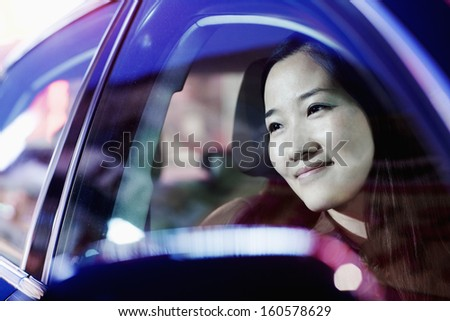 Smiling woman looking through car window at city nightlife - stock photo