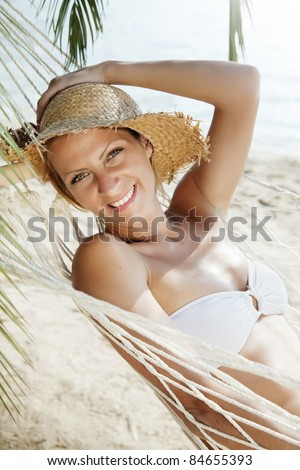 smiling woman lying in a hammock - stock photo