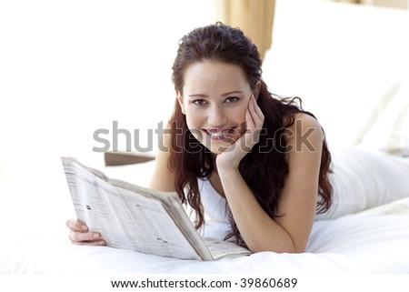 Smiling woman lying in bed reading a newspaper