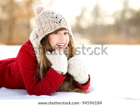 Smiling Woman Lying in the Snow - stock photo