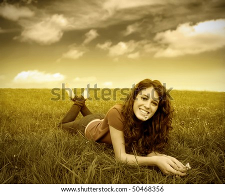 Smiling woman lying on a green meadow with a daisy in her mouth - stock photo