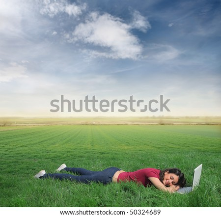 Smiling woman lying on a green meadow with a laptop in front of her - stock photo