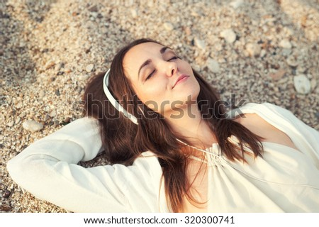 Smiling woman lying on a sea sand and listening music. - stock photo