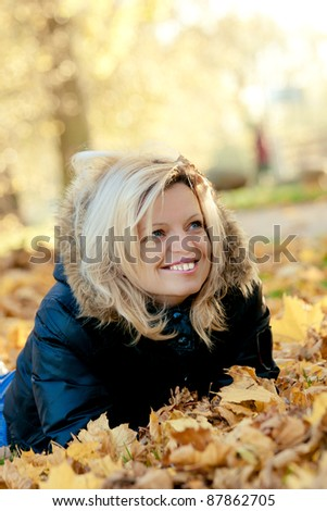 Smiling woman lying  on fall leaves - stock photo