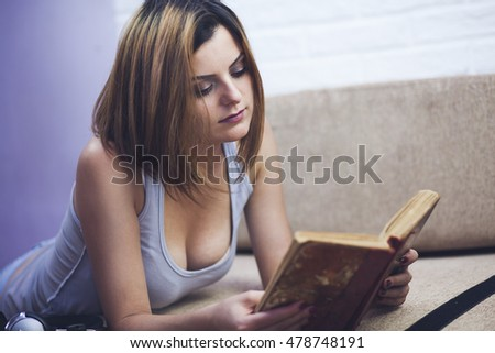 smiling woman, lying on her stomach, reading a book in bed