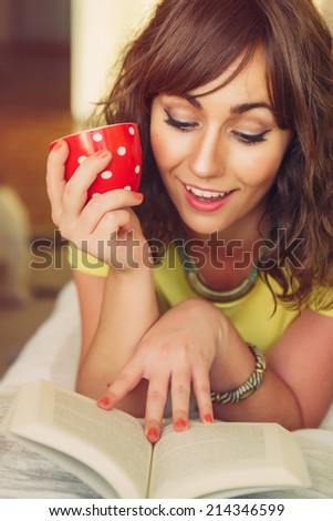 Smiling Woman Lying on Stomach and Holding Mug while Reading Paperback Book - stock photo