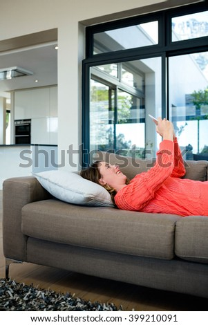 smiling woman lying on the couch taking a selfie