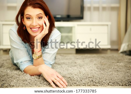 Smiling woman lying on the floor at home - stock photo