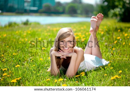 Smiling woman lying on the grass in a city park