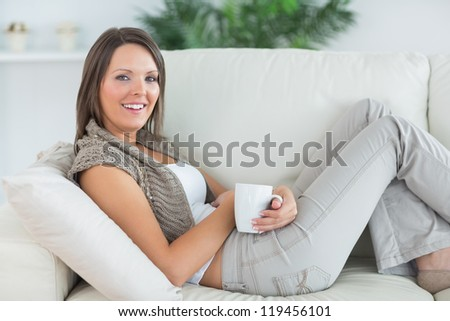 smiling woman lying on the sofa and holding a mug in the living room - stock photo