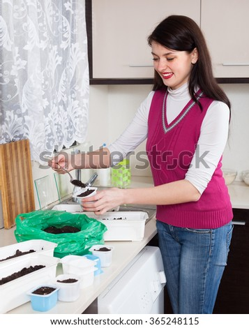Smiling woman making  ground for sprouts at home - stock photo