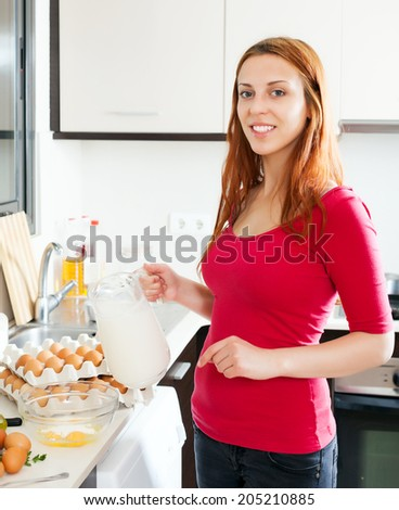 Smiling woman making omelet with milk in home kitchen